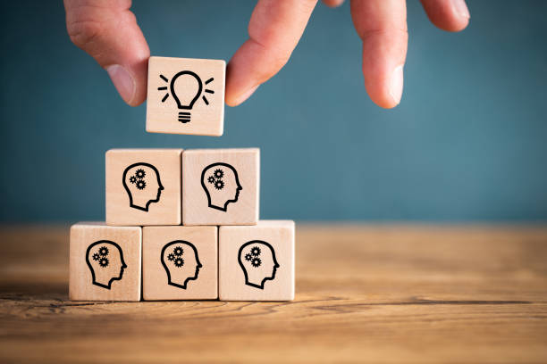 many people together having an idea symbolized by icons on cubes many people together having an idea symbolized by icons on cubes on wooden background finding stock pictures, royalty-free photos & images