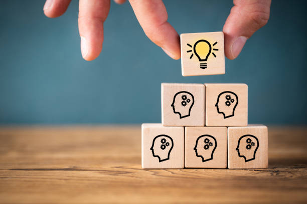 many people together having an idea symbolized by icons on cubes many people together having an idea symbolized by icons on cubes on wooden background brainstorming stock pictures, royalty-free photos & images