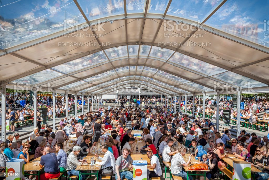 Many people together outdoors eating and drinking. stock photo
