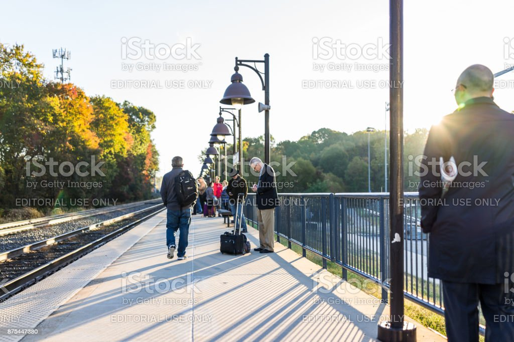 Many people waiting on platform for VRE train to Washington DC for commute at Burke Centre Station during morning stock photo