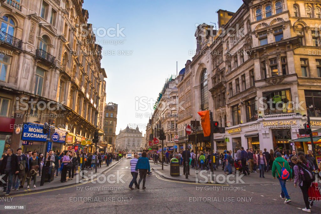 Many people walk around a busy area of London, England on Sunday evening stock photo