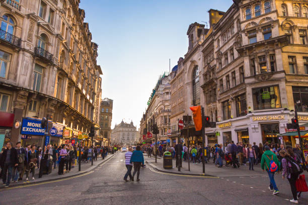 many people walk around a busy area of london, england on sunday evening - high up stock photos and pictures