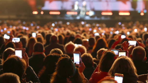 many people with smart phones at live concert stock photo