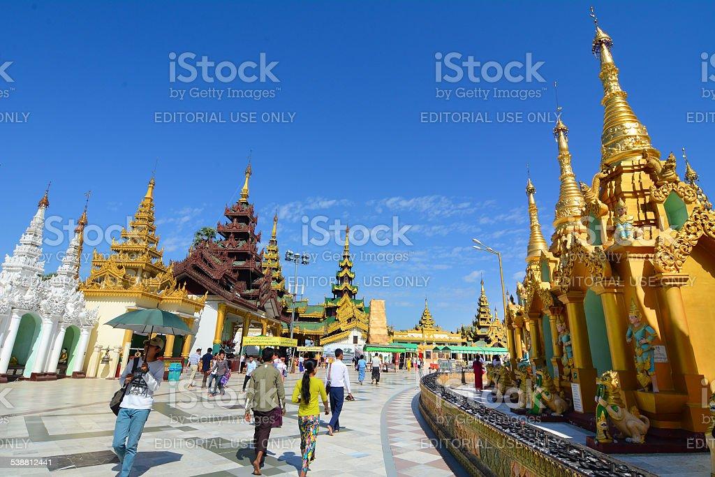 Many pilgrims walking around golden Shwedagon Paya stock photo
