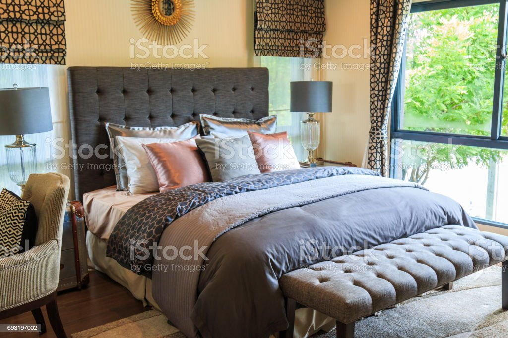 Many pillows on the bed and the bed head lamps with warm light. stock photo