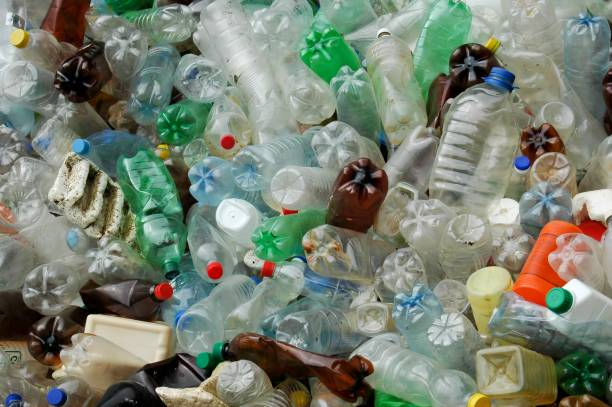 many plastic bottles thrown outdoor pollution of nature, many plastic bottles thrown outdoor near water need to rise awareness of recycle bottle bank stock pictures, royalty-free photos & images