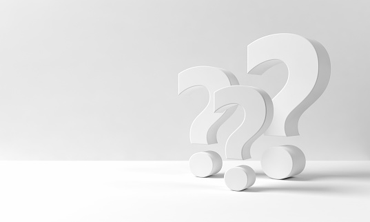 Multiple three dimensional question marks on a white backdrop resembling an indoor space with neutral background with copy space on the left side: questions, decisions, confusion.