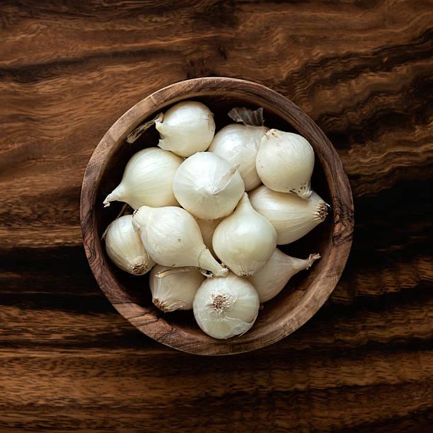 viele raw perlzwiebeln in eine hölzerne schüssel - perlzwiebeln stock-fotos und bilder