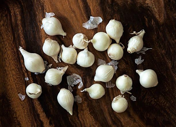 viele raw perlzwiebeln auf ein schneidebrett - perlzwiebeln stock-fotos und bilder