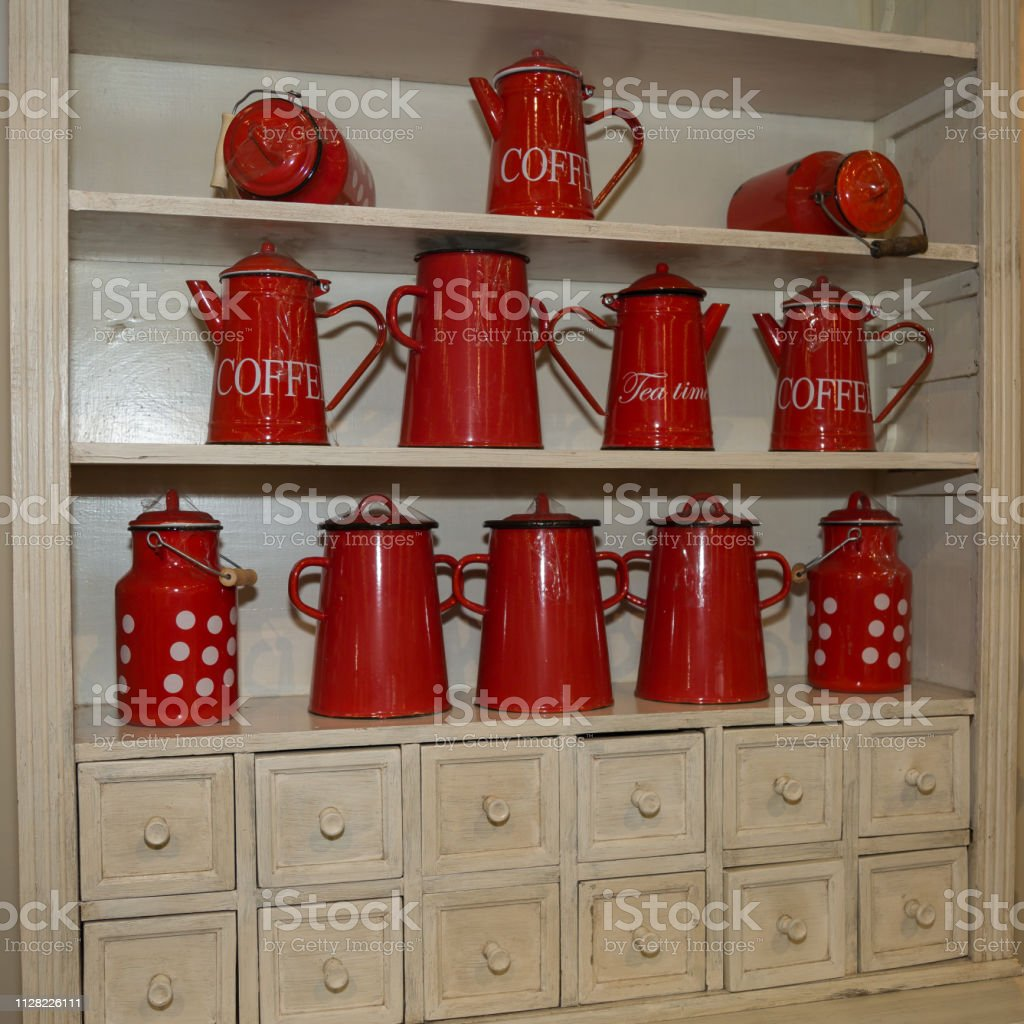 Many Red Coffee Makers and Red Metal Tea Containers on a Shelf.