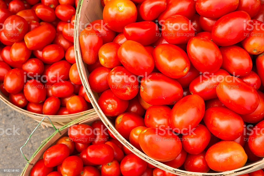 Many Roma tomatoes in baskets at the market stock photo