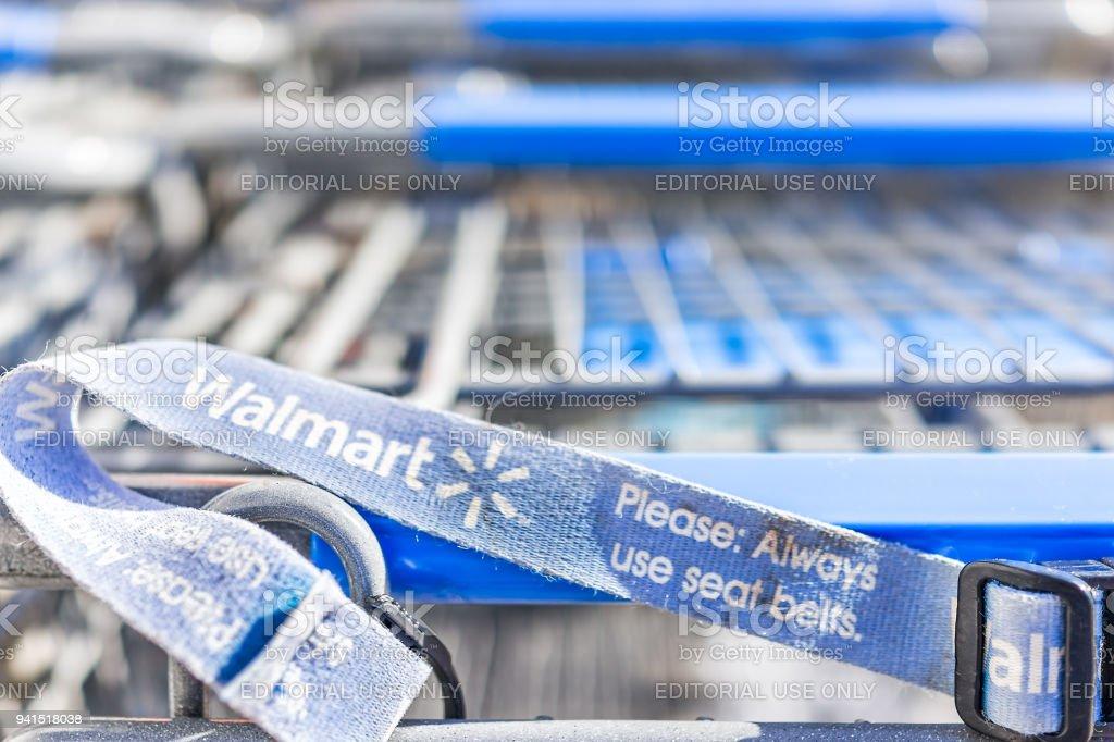 Muitas linhas de carrinhos de compras azuis fora por loja com sinal closeup pelo Walmart armazenam estacionamento em Virgínia - foto de acervo