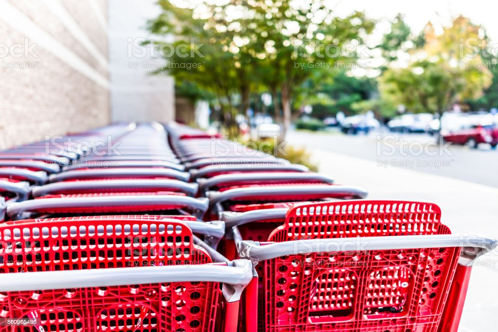 Many rows of red shopping carts outside by store with closeup by parking lot stock photo