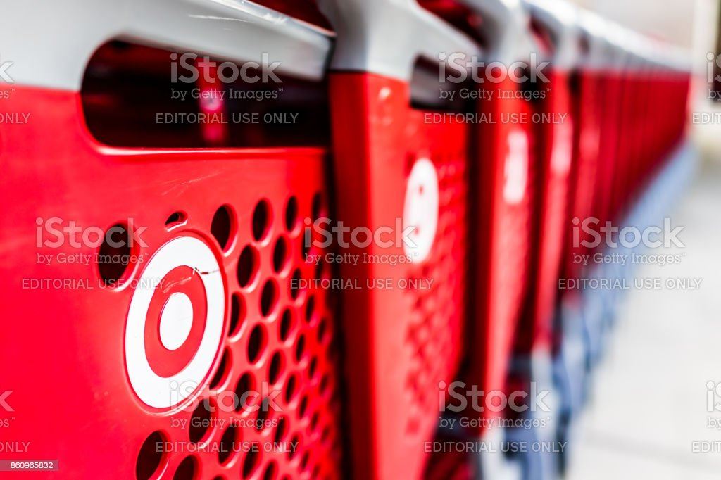 Many rows of red shopping carts outside by store with closeup by Target store parking lot stock photo