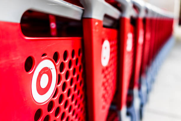 many rows of red shopping carts outside by store with closeup by target store parking lot - sports target stock photos and pictures