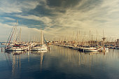 Many sail yachts in the sea harbor. Sailboat port. Summer vacation landscape with beautiful sky