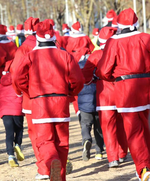viele weihnachtsmann mit rotem hut - laufveranstaltungen stock-fotos und bilder