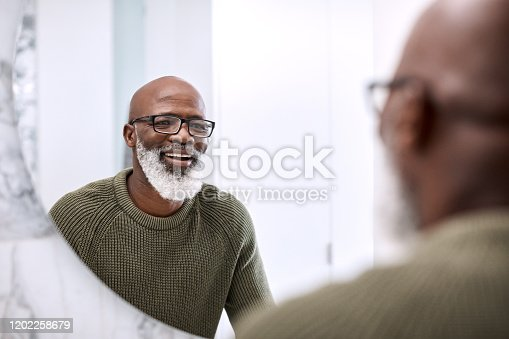 Shot of a mature man looking at his face in the bathroom at home