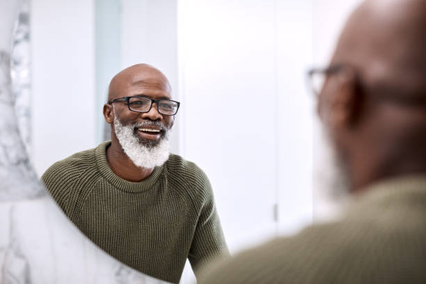 Many say that I look quite good for my age Shot of a mature man looking at his face in the bathroom at home mirror stock pictures, royalty-free photos & images