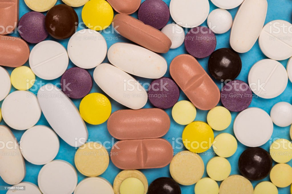 many scattered Colorful medical pills on blue background. Pills are...