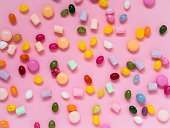 istock Many scattered colorful sweets, candies, lollipops, marshmallows on a pink background 863452096