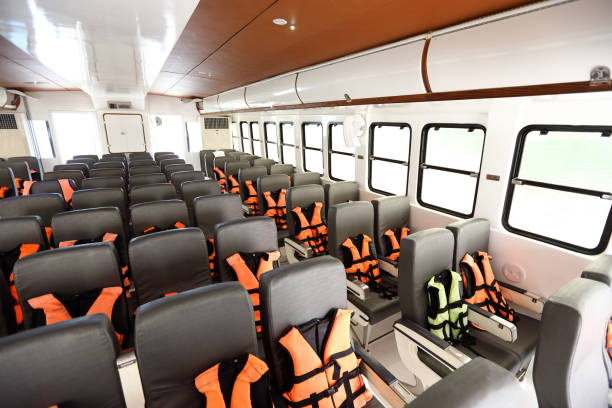 viele sitzplätze reihe innen luxus cruise fähre mit orangefarbenen schwimmwesten weste - rettungsinsel stock-fotos und bilder
