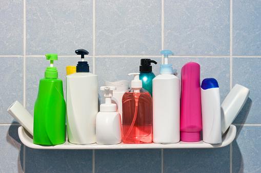 Many shampoo and soap bottles on a bathroom or shower shelf.