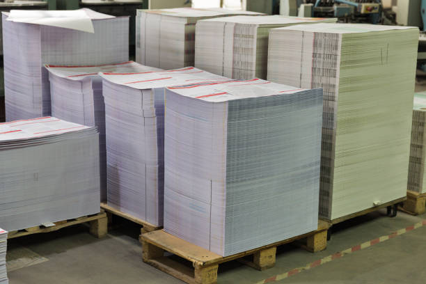 many sheets of white printed paper closeup stacks of printed sheets of cardboard on wooden pallets closeup. printing industry printing plant stock pictures, royalty-free photos & images