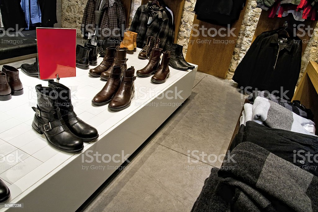 Many shoes and clothes on shop store shelves royalty-free stock photo