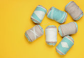 Many skeins of woolen threads of pastel colors on yellow studio background. Top view. Studio shot. Hobby homebrew