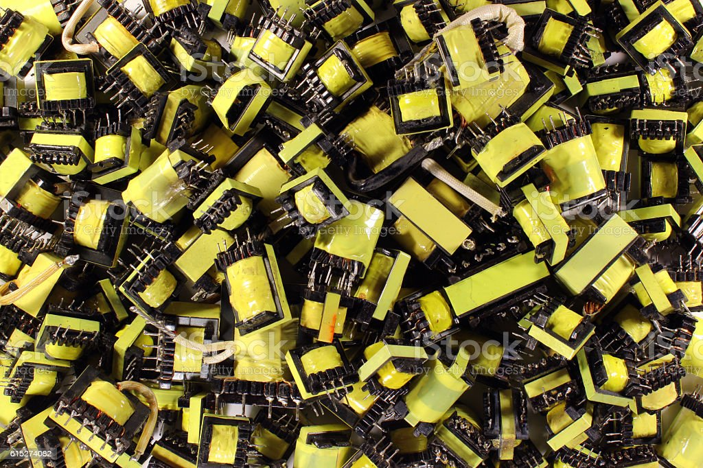 Many small yellow electrical ferrite transformers stock photo