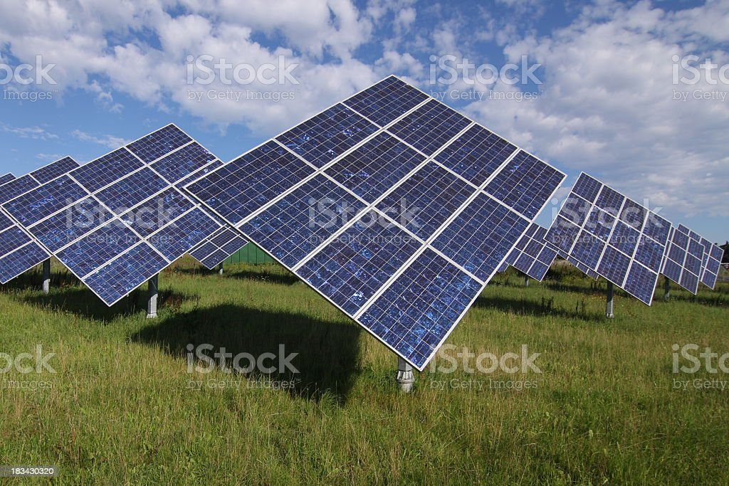 Many solar panels placed on a green field with a blue sky royalty-free stock photo