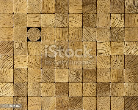 Many square wood blocks stacked up with one different round block the other square blocks. Concept image of individuality, going against the grain, standing out from the crowd etc.
