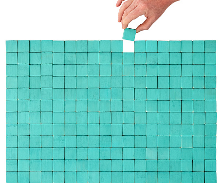 Many square wood textured colorful turquoise-colored wooden blocks stacked up on top of each other to make a rectangle shape with one block missing, whilst a hand is placing the final missing block into the empty space, building it back up to completion. A creative concept relating to building, building up, completing, business strategy, puzzle, finding the missing pieces, etc. Isolated on white, clipping path included.