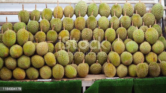 Many stacked Durian fruits at market stall in Singapore Geylang