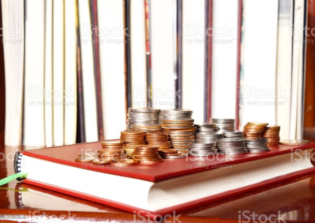 Many stacks of coins in various sizes and valued,Coin on a book cover red stock photo