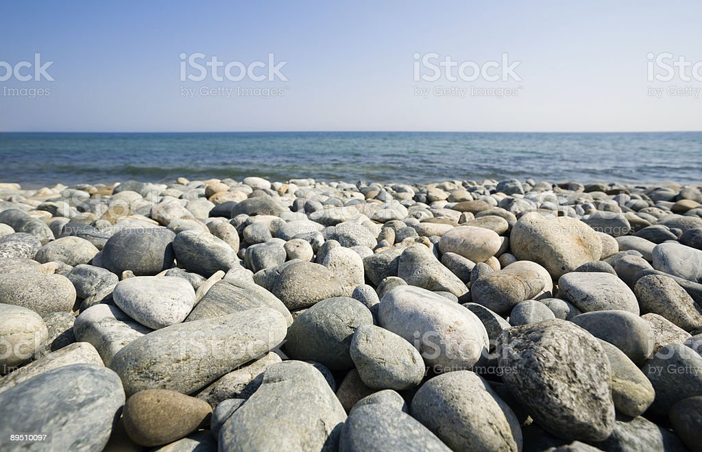 Many stones on the beach by the water royalty-free stock photo