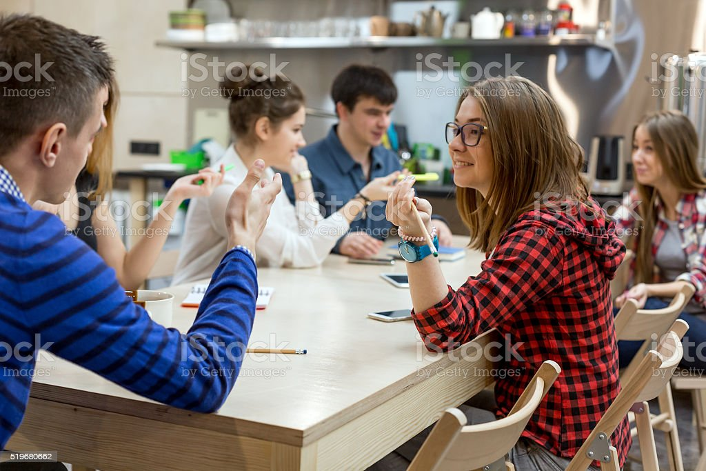Many Students sitting at Wood Table of Campus and talking stock photo