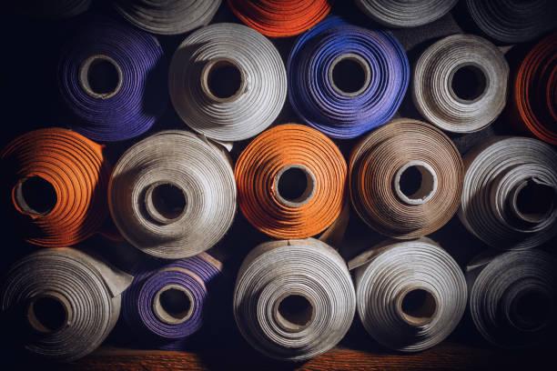 many textile rolls of blue, white and orange colors stacked one over the other - przemysł włókienniczy zdjęcia i obrazy z banku zdjęć