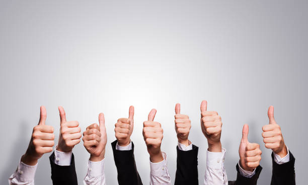many thumbs up in front of grey background many thumbs up in business sleeves in front of grey background fan club stock pictures, royalty-free photos & images