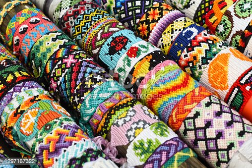 Many tied woven DIY friendship bracelets handmade of embroidery floss. Alpha and normal patterns