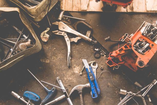 viele tools auf schmutzigen boden, legen sie handwerker werkzeug, mechanische werkzeuge. professionellen mechaniker mit verschiedenen werkzeugen für die arbeit in auto-reparatur-service. - autos und motorräder stock-fotos und bilder
