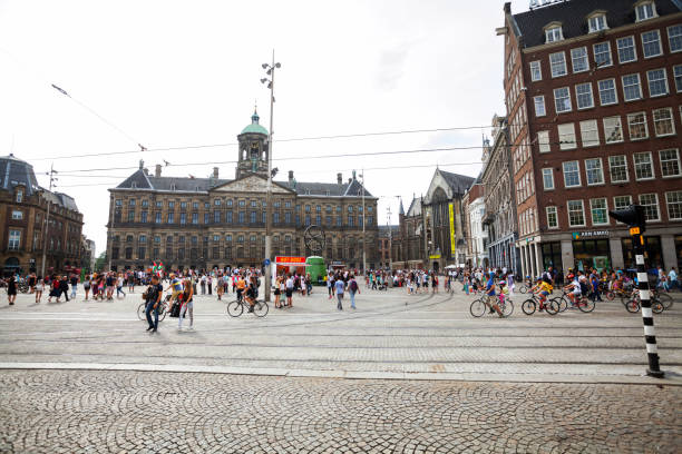 many tourists and cyclist near royal palace in amsterdam - dam photos et images de collection