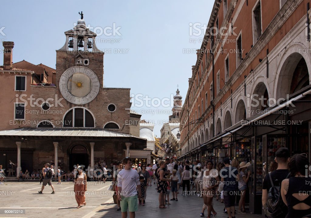 Many tourists and gift shops by San Giacomo di Rialto Church in Venice / Italy. Catholic gothic building dating to circa 1071 CE, with a large, iconic 15th-century clock on its facade. stock photo