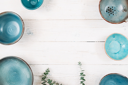 Many turquoise empty ceramic plates. Flat lay