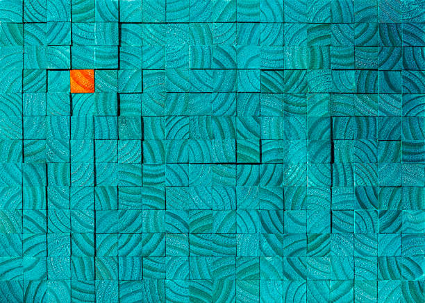 Many turquoise wooden blocks or profiles with a wood grain pattern showing, with one opposite color orange wooden block in contrast sitting amongst the the turquoise blocks.. stock photo