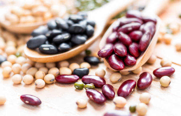 many types of beans are separated in a spoon on a wood table such as mung bean, soybean, black bean, red bean. selective focus. - bean stock photos and pictures