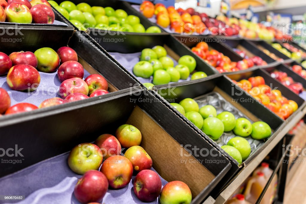 Many varieties assorted apples on display shelf in grocery store boxes in aisle, supermarket inside, nobody, including granny smith green and macintosh red fruit stock photo