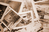 Many vintage, sepia-toned photographs from the 1940s lying in a large pile.  Old-fashioned memories from the past.  Antiques.  No people in this toned image and any people in the photos are unrecognizable.  Photos are of home lifestyles, vehicle in the 1940s.