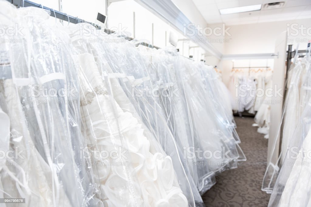 835141f7dc Many wedding dresses gowns in boutique discount store, white garments  hanging on rack hangers row closeup with white lace, tulle, design - Stock  image .
